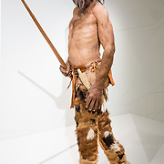 In the South Tyrol Museum of Archaeology in Bolzano, Italy, a reconstruction shows the famous Iceman at age 45. Ötzi dates from 3300 BC and is Europe's oldest natural human mummy. The Iceman was found in 1991 fully clothed, melted out from a glacier in the Ötzal Alps, Europe. The 5000-year-old Iceman was apparently murdered at age 45 by an arrowhead lodged in his left shoulder. His copper axe pushed back the Bronze Age by 1000 years. The Iceman's tools were a delight for archeologists: a copper axe with a yew handle, a flint-bladed knife with an ash handle, a quiver of 14 arrows (with viburnum and dogwood shafts, two with fletching fins and tipped with flint), an antler tool for sharpening arrow points, an unfinished yew longbow 1.82 meters (72 in) long, a bow string, berries, two birch bark baskets, two species of polypore mushrooms strung on leather (for medicinal and tinder use), and a complex firestarting kit (with pieces of a dozen different plants plus flint and pyrite to make sparks). His valuable 9.5-centimeter axe head is almost pure copper, made by casting, cold forging, polishing, and sharpening. His copper axe's handle (haft) is 60 centimetres (24 in) long and made from carefully worked yew. Anthropologists were surprised at the sophistication of Ötzi's clothes, including: a woven grass cloak, a coat, a belt with tool pouch (scraper, drill, flint flake, bone awl and a dried fungus), a pair of leggings, a loincloth and shoes, all made of leather of different skins sewn together with sinew, plus a bearskin cap with a leather chin strap. His shoes were waterproof and wide for snow, made with bearskin soles, deer hide on top panels, plus netting made of tree bark. Soft grass cushioned the foot like modern socks. View the actual frozen mummy and possessions of Ötzi in Bolzano, the Dolomites, in Trentino-Alto Adige/Südtirol (South Tyrol) region of Italy, Europe.