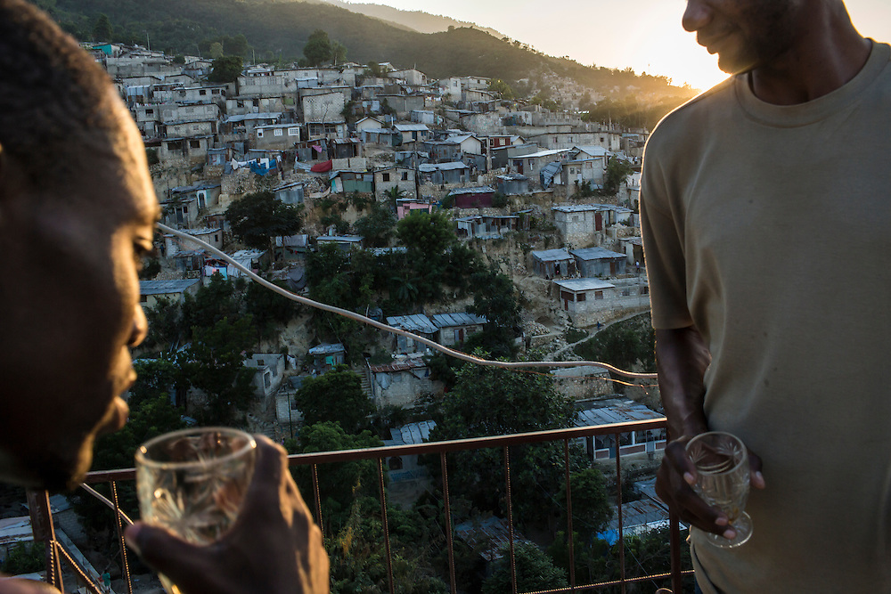 Jerry Cojoux, left, and Benoit Jean Wilfrid drink whiskey on the roof of Winfrid's restaurant as the sun sets in the Tapis Rouge neighborhood on Friday, December 19, 2014 in Port-au-Prince, Haiti.