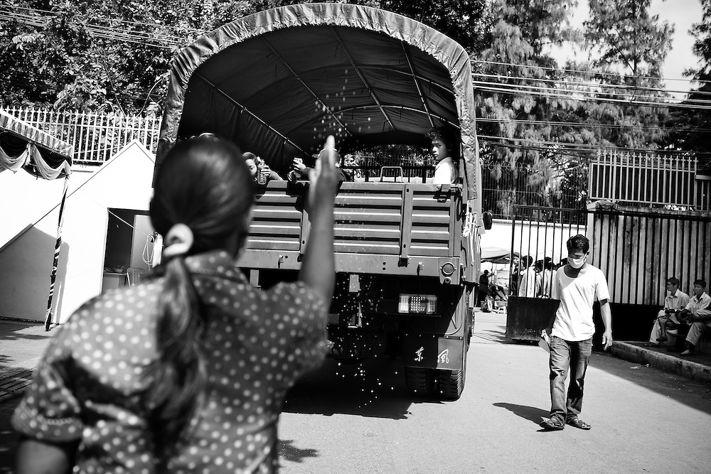 A woman throws rice in offering as a government truck carrying the body of one victim and her family depart for their hometown of Kampong Chom, several hours from Phnom Penh, Cambodia. Several hundred perished in a stampede tragedy when an unknown event sparked panic and thousands attempted to flee Diamond Island in the middle of the Mekong River over the bridge connecting it to the river bank.