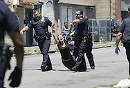 Newburgh Police officers drag an unidentified female EDP or emotionally disturbed person to a waiting ambulance on City Terrace, near Van Ness Street in the City of Newburgh, NY on Thursday, June 7, 2012. Orange County Sheriff's deputies are continuing their patrols of the city along with Newburgh Police.