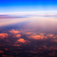 Aerial view of a distant aircraft in flight over cumulus clouds illuminated by the last rays of the setting sun.