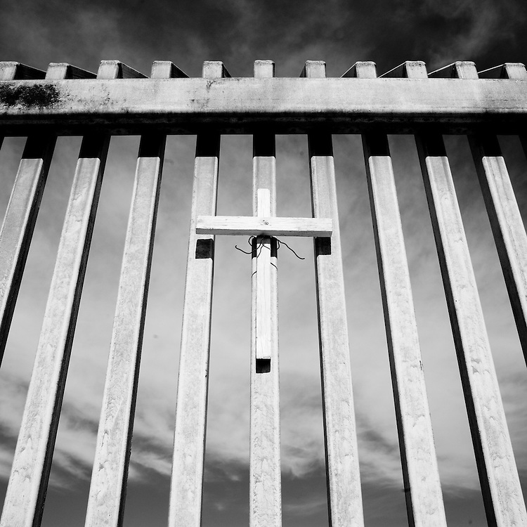 A cross hangs on the fence marking the border between the United States and Mexico in Agua Prieta, Sonora, Mexico, on Wednesday, Jan. 30, 2008.