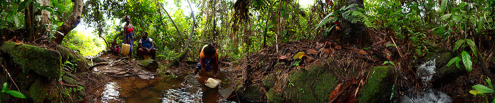 Agnes collects water from a stream while her friends wait for their turn, Manamu, Liberia.