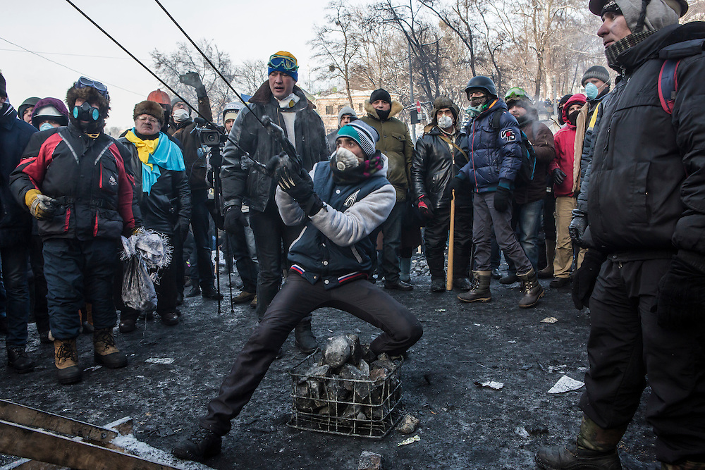 KIEV, UKRAINE - JANUARY 25: An anti-government protester uses a large sling shot during clashes with police on Hrushevskoho Street near Dynamo stadium on January 25, 2014 in Kiev, Ukraine. After two months of primarily peaceful anti-government protests in the city center, new laws meant to end the protest movement have sparked violent clashes in recent days. (Photo by Brendan Hoffman/Getty Images) *** Local Caption ***