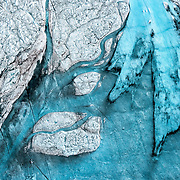 Blue meltwater and dark deposits of soot and ash flow into an unnamed seasonal lake atop the Greenland ice sheet, 80km southeast of Ilulissat, August, 2014.