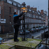 British Gas employee turns on a gas lamp in the Westminster area, London.