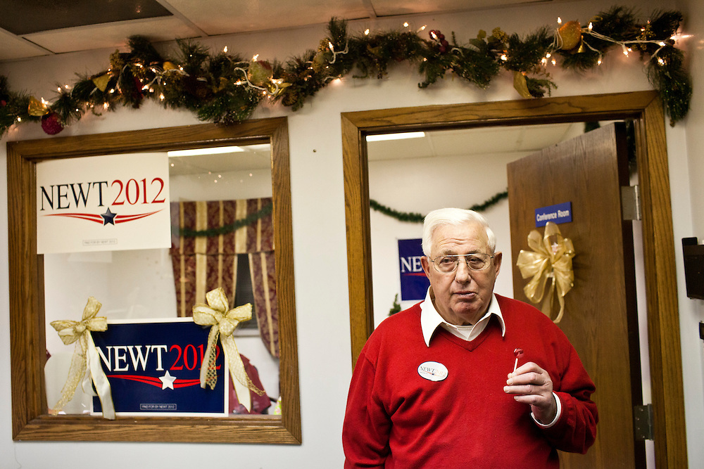 A man eats a lolly pop as he waits for Republican presidential candidate Newt Gingrich to arrive for a rally at his campaign office on Monday, January 2, 2012 in Davenport, IA.
