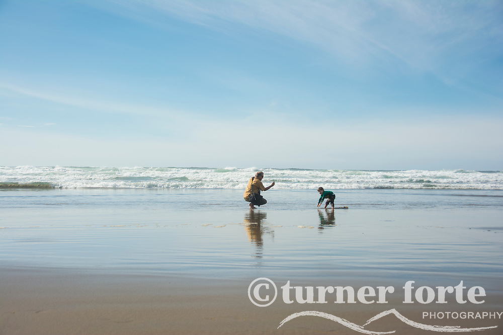 Father takes photo with phone of toddler son digging in sand, Cannon Beach, Oregon.