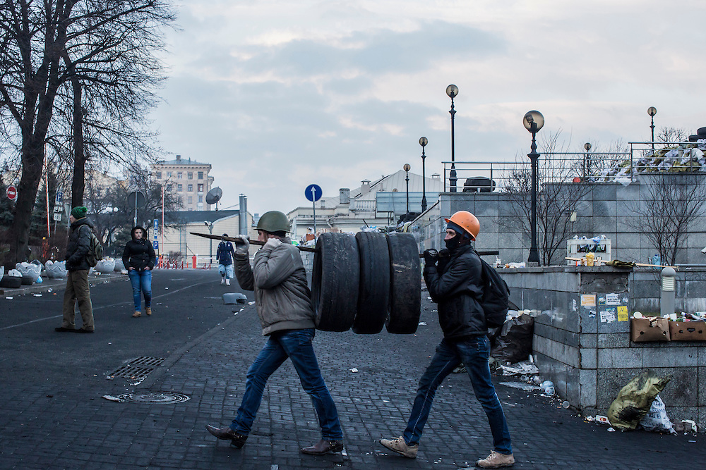 KIEV, UKRAINE - FEBRUARY 21: Anti-government protesters carry tires to the barricades Independence Square on February 21, 2014 in Kiev, Ukraine. After a week that saw new levels of violence, with dozens killed, opposition and government representatives reached an agreement intended to resolve the crisis. (Photo by Brendan Hoffman/Getty Images) *** Local Caption ***