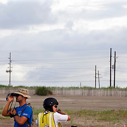 From left, a contracted security worker and a clean up worker look along the shore on June 23, 2010 in Grand Isle, LA where oil has reached land.  Both declined comment. The Deepwater Horizon and the British Petroleum oil spill has been claimed as the most damaging environmental disaster in history.