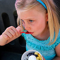 Young girl enjoys refreshing ice cream and fruit on a warm summer's day.