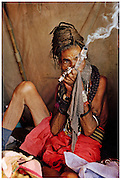 Known as the 'bloody mela' because of the soaring heat, the Ujjain mela is one of the four of Indias Hindu Khumb Mela festivals.<br /> This greatly revered Sadhu can be seen smoking an intoxicating mixture of tobacco and Charas (Hashish) from a pure silver Chillum - 2004