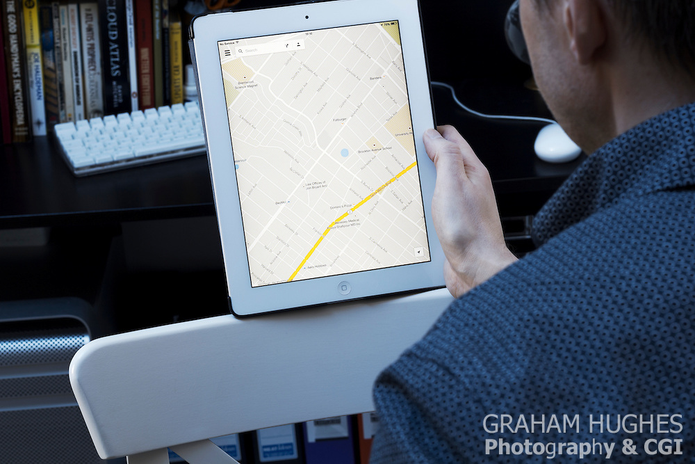 Male using iPad 2 at desk with Google maps on screen.
