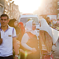 Women make their way through an impoverished neighborhood in Cairo, Egypt. September 2012.