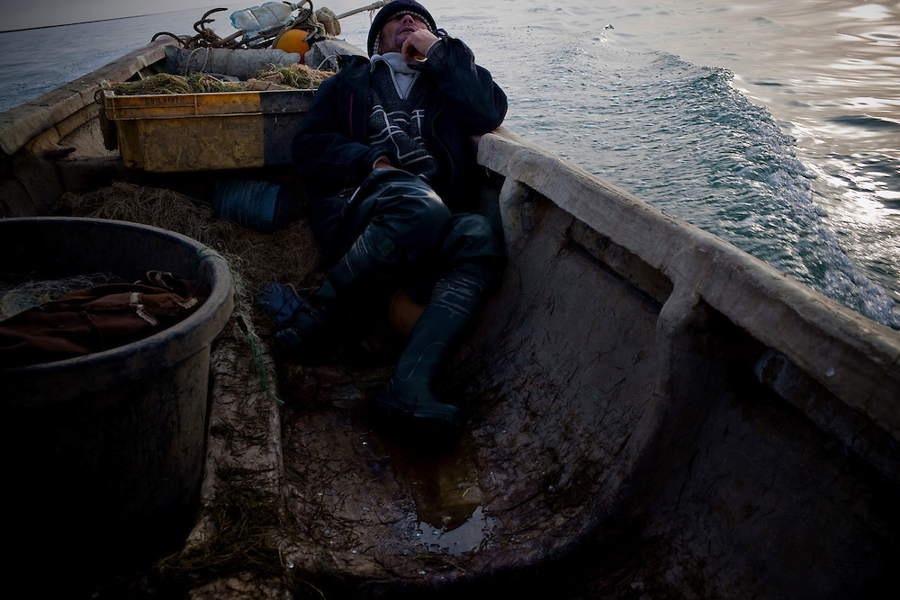 CREDIT: DOMINIC BRACCO II..SLUG:PRJ/KAZAKHSTAN..DATE:..CAPTION:Sahi Aidoraliev, 53 of Aralsk, passes out drunk while out at sea on November 1, 2009...Aral Sea Overview: ..During the 1960s the USSR began irrigating the waters of the Aral Sea in southern Kazakhstan to combat their growing food crisis. The Soviets severely miscalculated and water began receding quickly from the port cities. The waters continued to recede. By 2000 the water was 80 km away from the city of Aralsk, a main seaport in Kazakhstan. In 2005 with help from the World Bank, construction began on a 13km dike that locals hoped would bring the waters back to their original shores. The project raised water quality and fishing was able to resume, however four years after completion of the dike the water is still 50km from Aralsk's port. Locals seem mixed on the possibility of the sea returning after more than 40 years without the sea. Fishermen from Aralsk make a three-hour path through soft desert road along the former seabed. The only source of income for many is cattle, horses, and camels, which have, began to overgraze the areas of the former seabed and surrounding desert. Because of this nutrient rich topsoil is lifted by the wind and the process of desertification continues.  .