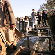 Pedestrians cross a bridge in the historic bazaar district in Kabul, Afghanistan.  Much of the city's infrastructure crumbled after decades of fighting. Photographed November 20, 2001.