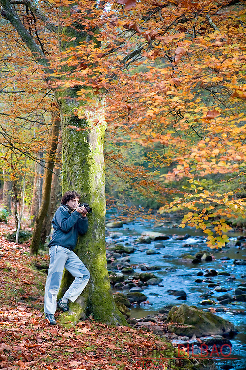 young woman taking photographs of a forest in autumn.<br />