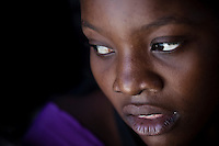 A Haitian girl looms out of the darkness in the back of a tap tap in Jacme,
