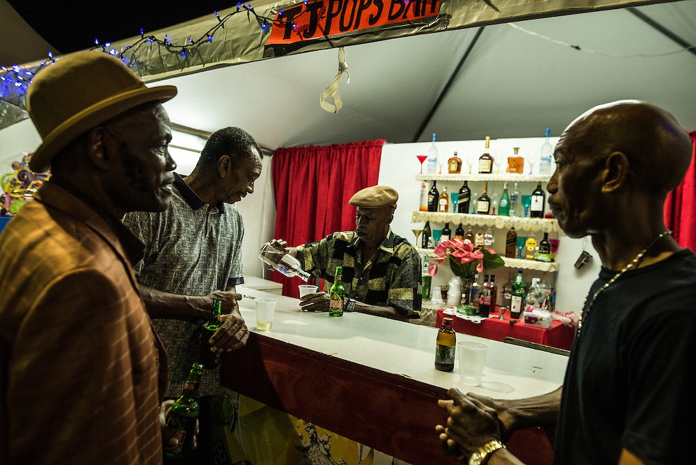 "PORT OF SPAIN, TRINIDAD - FEBRUARY 15, 2017: Men share jokes and beers while partying (called ""liming"") in Queen's Park Savannah.  PHOTO: Meridith Kohut for The New York Times"