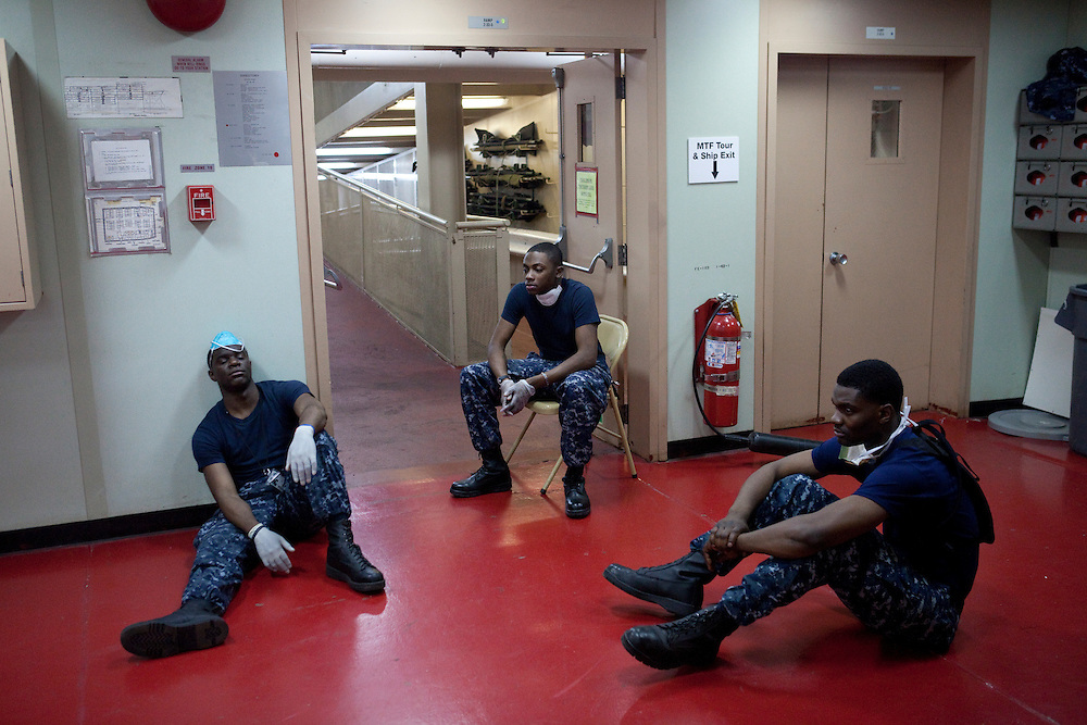 English/Creole translators take a rest in the casualty receiving area on board the USNS Comfort, a naval hospital ship, on Wednesday, January 20, 2010 in Port-Au-Prince, Haiti. The Comfort deployed from Baltimore, bringing nearly a thousand medical personnel to care for victims of Haiti's recent earthquake.