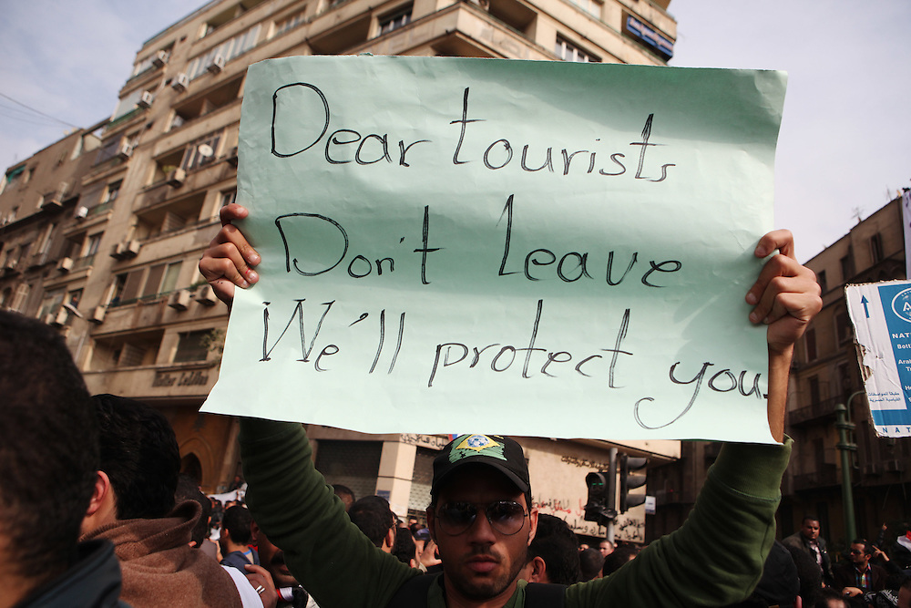 A protester holds a sign asking tourists not be scared.
