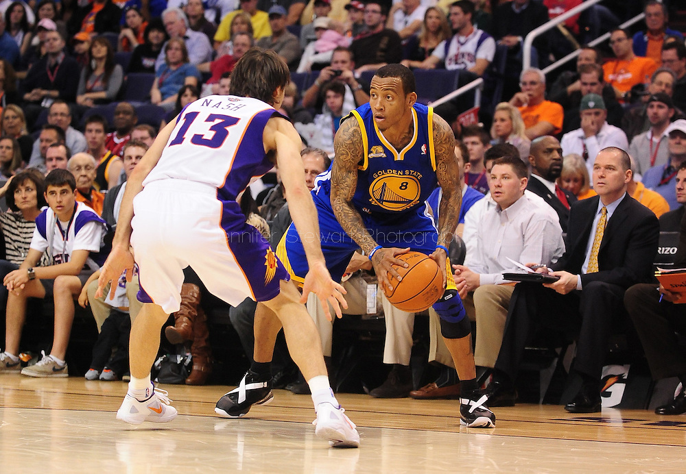 Jan. 2, 2012; Phoenix, AZ, USA; Golden State Warriors guard Monta Ellis (8) reacts on the court against the Phoenix Suns guard Steve Nash (13) at the US Airways Center. The Suns defeated the Warriors 102-91. Mandatory Credit: Jennifer Stewart-US PRESSWIRE.