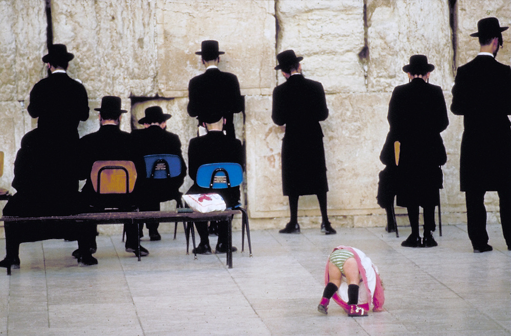 Hassidic men worship by reciting prayers at the Wailing Wall in Jerusalem Israel. A young girl plays innocuously baring her striped underpants juxtaposed against the traditional somber black clothes worn by the men. Men and women are segregated in this area of worship. <br /> <br /> Tel 0044(0)208 944 6933<br /> www.linkphotographers.com Photography by Orde Eliason
