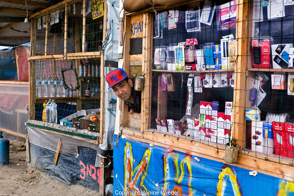 Afgan Shopkeeper in Makeshift shop selling general supplies in The Calais Jungle Refugee and Migrant Camp in Franceinside