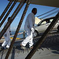 Workers unload cars form a cargo ship at the port of Manta, Ecuador on April 15, 2008. (Photo/Scott Dalton).