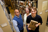 Tad Boehmer '12 poses for a portrait alongside his MAP advisors, classics professor Angelo Mercado and librarian Catherin Rod, in the archives vault in the basement of Burling Library. Boehmer's project sought to determine the origin and use of an unidentified, 488-page manuscript written primarily in Latin..BEN BREWER/Grinnell College