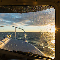 Canada, Nunavut Territory, Repulse Bay, View from helm of C-Dory expedition boat motoring through Hudson Bay on summer evening