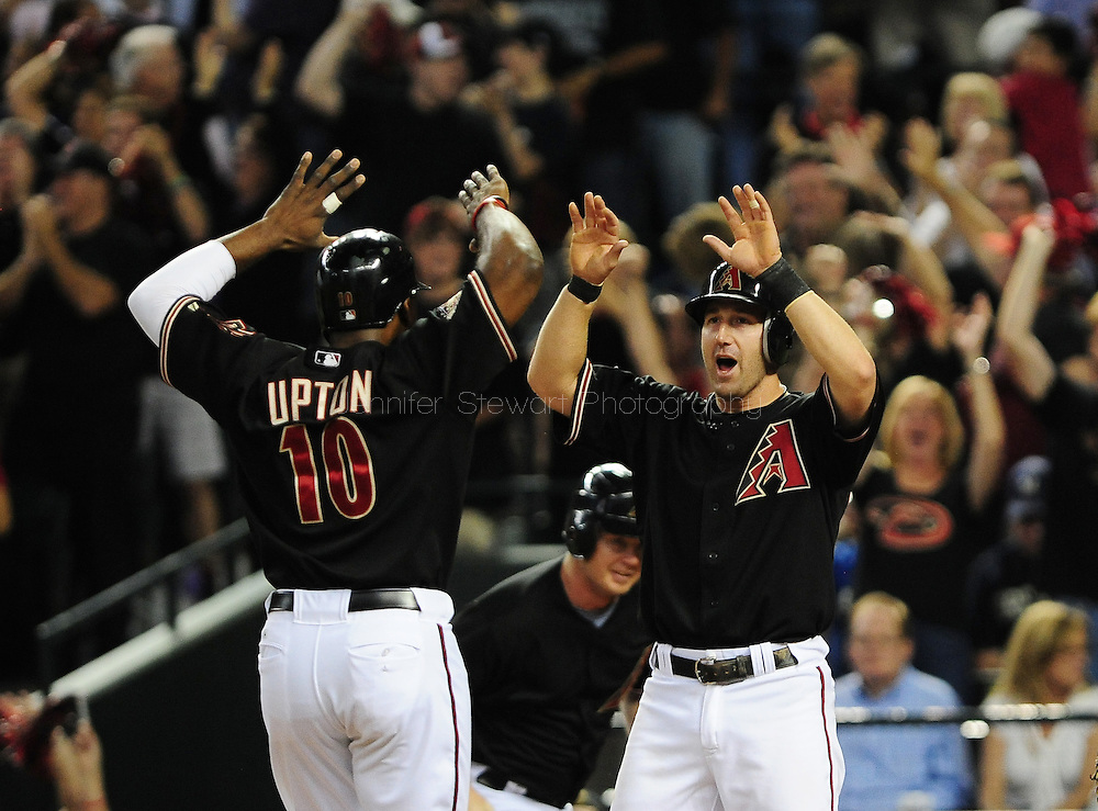 Oct. 5 2011; Phoenix, AZ, USA; Arizona Diamondbacks outfielder Justin Upton (10) and teammate infielder Willie Bloomquist (18) celebrate after scoring  during the first inning against the Milwaukee Brewers at game four of the 2011 NLDS at Chase Field. Mandatory Credit: Jennifer Stewart-US PRESSWIRE.