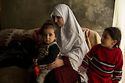 Aley, LEBANON: Maamna Al Msalem, 31, with her duaghters, 11-month old Raghdaa and four-year old Maryam. They came from Saaba, outside of Damascus. They left at the beginning of 2012. The father was a carpenter and did cabinetry and similar work.<br /> He lost his mind not long after they arrived in Lebanon. He would routinely walk around town, his fist raised in the air, cursing Bashar and screaming obscenities. Locals made fun of him or beat him up. Eventually, he was hospitalized, where he was diagnosed with an acute neurodegenerative disease. His wife thinks it was the stress of leaving home and being unable to find work to support his family that led to his illness.<br /> <br /> She says that when they speak on the phone, she can&rsquo;t understand what he is saying - he doesn;t make any sense. Once, he called, asking about their youngest daughter. He claimed to have seen her murdered. He was in an absolute panic. Now, his wife doesn&rsquo;t answer the phone anymore when he calls. It&rsquo;s too upsetting. Liam Maloney/Polaris Images