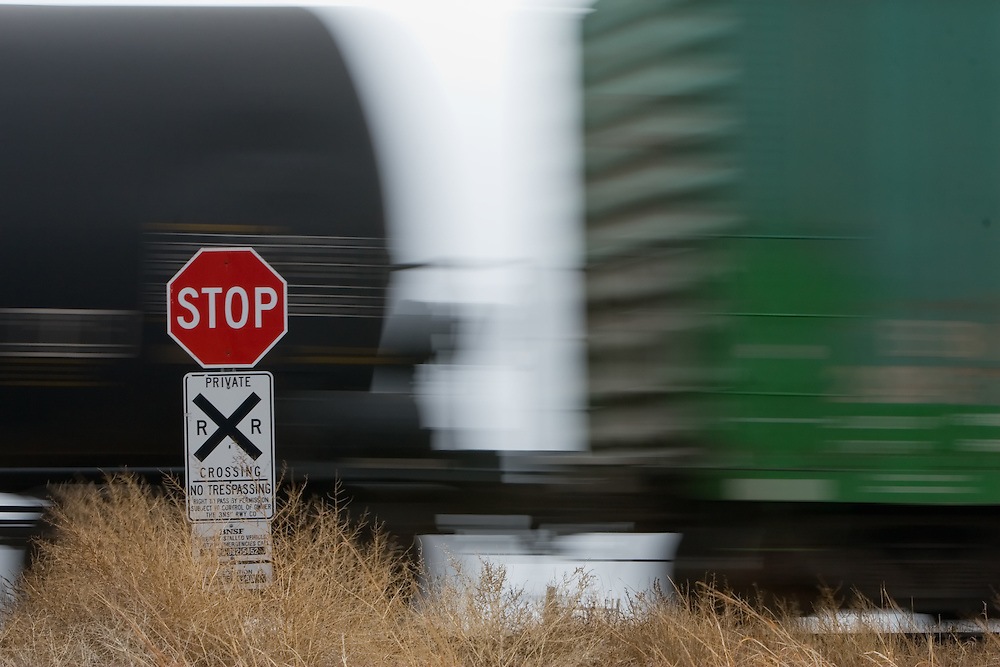 Flashing past a private railroad crossing on a farmers ranch road, an eastbound BNSF freight train makes its way across Nebraska.