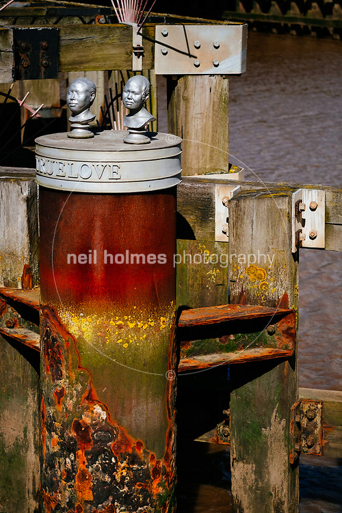 River Hull, Kingston Upon Hull, East Yorkshire, United Kingdom, 26 August, 2015. Two  heads sit on top of the wooden barrier next to the tidal surge barrier on the west side of the River Hull. By artist Stefan Gec (2002).