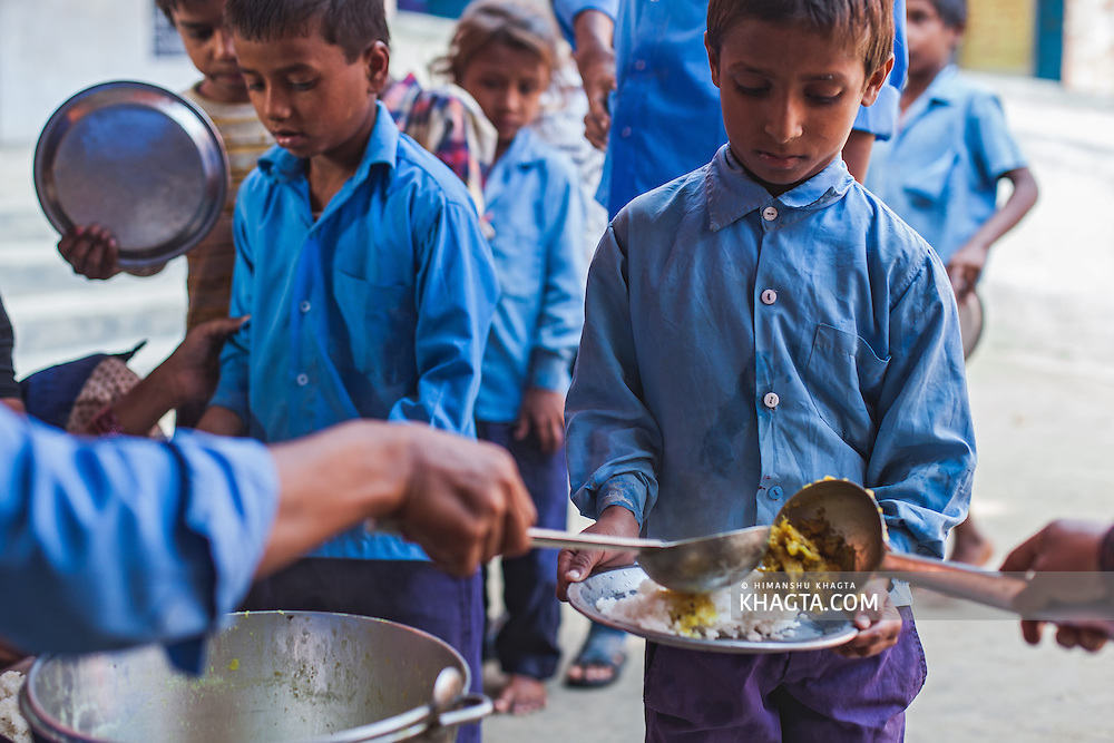 Primary school children having their mid day meal. Government of India, under their Mid Day Meal program, provides free meals daily to school children across the country.