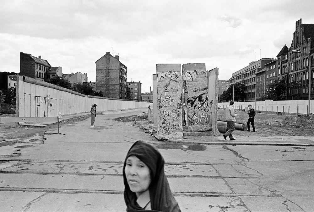 Deutschland - GERMANY - Mauerfall - 1990 -  Die Berliner Mauer verschwindet aus dem Stadtbild, die Mauer wird abgerissen/abgetragen : HIER:  Neue Wege zwischen Kreuzberg und Friedrichshain; Adalbertstraße/Engeldamm; Türkische Frau und Touristen; 08/1990.1990 - FALL OF THE BERLIN WALL - the wall disappears, is demolished; HERE: new ways between the eastern & western districts; Turkish woman and tourists; 08/1990.copyright: Christian Jungeblodt