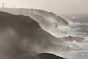 Storm waves crash onto the imposing, rugged once tin mining cliffs at Pendeen, West Penwith, Cornwall. The last mine closed years ago, but numerous engine houses and chimneys mark the site of this once booming Cornish industry providing high grade tin.