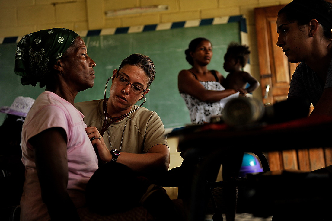 First Lt. Daniela Feldhausen, a physician assistant, listens to a Honduran womans breathing as another woman and child wait their turn during a physician consultations in the costal village of Batalla, Honduras. Over the two day visit at this location, the medical team saw 533 in preventative medicine,251 Screening, 265 physician consultations, 287 pharmacy and 74 dental services. — © /