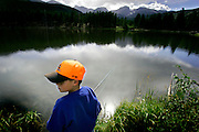 "Eight year-old Alexander Moody of Springfield, Ill. fishes for trout in Sprague Lake at Rocky Mountain National Park on Thursday August 18, 2005. Moody was vacationing with family at the park and his mom, Conny, said, ""this is a great park for families"". The park, open since 1915, is a showcase of the grandeur of the Rocky Mountains and features peaks ranging from 8,000 to 14,259 feet tall and is home to elk, mule deer, bighorn sheep, black bears, coyotes and a wide range of birds, fish and smaller animals.  Rocky Mountain National Park is located in the north-central region of the U.S. state of Colorado..Rocky Mountain National Park features majestic mountain views, a variety of wildlife, varied climates and environments?from wooded forests to mountain tundra?and easy access to back-country trails and campsites. The park is located north-west of Boulder, Colorado in the Colorado Rockies, and includes the Continental Divide and the headwaters of the Colorado River in its land area.Rocky Mountain National Park encompasses approximately 265,770 acres (1,076 km²) of land in Colorado's northern Front Range. The park is split by the Continental Divide, which gives the eastern and western portions of the park a different character. The east side of the park tends to be dryer, with heavily glaciated peaks and cirques. The west side of the park is wetter and more lush, with deep forests dominating..The park contains 359 miles (578 km) of trails, 150 lakes, and 450 miles (720 km) of streams. The park contains over 60 named peaks higher than 12,000 feet (3,700 m), and over one fourth of the park resides above tree line. The highest point of the park is Longs Peak, which rises to 14,259 feet above sea level. Longs Peak is the only fourteen thousand foot peak in the park..(MARC PISCOTTY/ © 2005)"