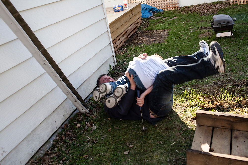Steve McFarland wrestles with his son Joe in their back yard on Friday, March 23, 2012 in Webster City, IA.
