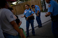 "From right, officers Alberto Cortez Jr., Jose De La Cruz, and Claudia Gonzalez speak with a family that claims they were threatened by a subject claiming to be affiliated with the Mexican criminal organization ""Los Zetas"" after an argument on August 19, 2010 in Laredo, Texas. The officers at the scene said in recent months there has been an increase in similar claims."