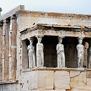 """Caryatids support the southern portico of the Erechtheion, the most sacred sanctuary on the Acropolis, in Athens, Greece, Europe. The Erechtheion and the """"Porch of the Maidens"""" was built entirely of marble between 421 and 406 BC. Between 1800 and 1803, one of the caryatids was removed by order of Lord Elgin to decorate his Scottish mansion, and was later sold to the British Museum in London (along with the pedimental and frieze sculpture taken from the Parthenon). Athenian legend had it that at night the remaining five Caryatids could be heard wailing for their lost sister. Elgin attempted to remove a second Caryatid; but when technical difficulties arose, he tried to have it sawn to pieces. The statue was smashed, and its fragments were left behind. It was later reconstructed haphazardly with cement and iron rods. In 1979, five original Caryatids (sculpted female figures serving as an architectural support) were moved to the Acropolis Museum in Athens and replaced in situ by exact replicas. The Acropolis of Athens and its monuments were honored as a UNESCO World Heritage Site in 1987."""