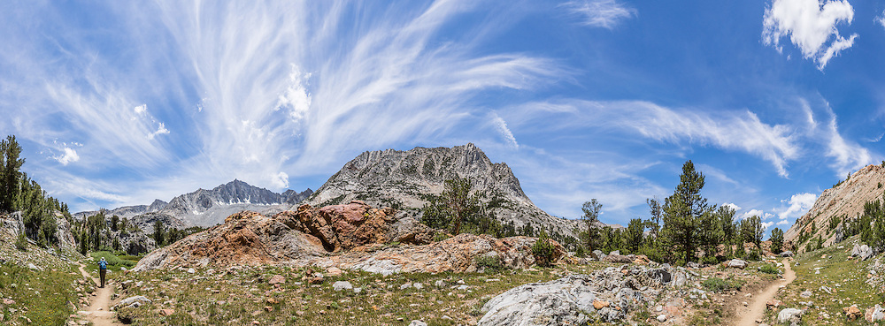 Cirrus clouds streak over Mount Goode (13,085 feet) and Hurd Peak (12,237 ft, center) along a scenic trail in the High Sierra. My favorite hike in the Bishop Creek watershed goes from South Lake to Long Lake and Saddlerock Lake, looping back via a steeper, poorly marked route to Ruwau Lake, Chocolate Lakes, and Bull Lake, in John Muir Wilderness, Inyo National Forest, Sierra Nevada, California, USA. The rewarding semi-loop is 9 miles with 2220 feet cumulative gain. An easier walk is 7.2 miles round trip with 1500 feet gain to Saddlerock Lake, out and back via beautiful Long Lake. This panorama was stitched from 12 overlapping photos.