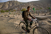 An Afghan boy rides through a cemetery in Kabul, Afghanistan.