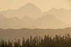 Peaks of the Fairweather Range bask in sunset light in Glacier Bay National Park and Preserve in this view seen from Glacier Bay Lodge located in Bartlett Cove of the park in southeast Alaska.