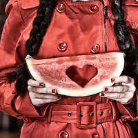 Two friends holding watermelon slices with a carved heart and the word love.