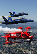 An aerobatic pilot in his Team Oracle plane, flies in formation over Seattle with the Blue Angels.<br />