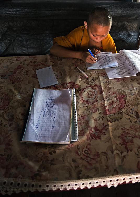 A novice studies at Wat Xiengmouane Vajiramangalaram in Luang Prabang, Laos.