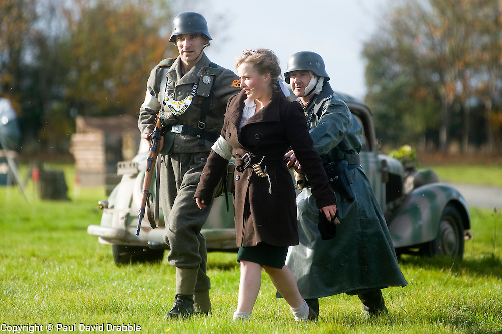 Pickering 1940s war weekend Northern World war Two Association battle reenactment. Members of the German Feldgendarmerie or field police living history group capture a female partisan or resistance fighter and lead her away for interrogation October 2009 Image Copyright Paul David Drabble